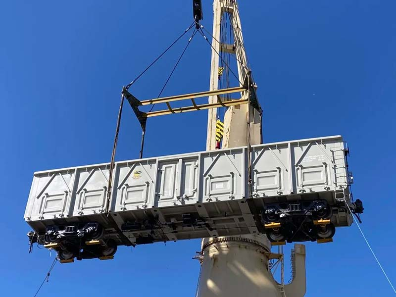 a freight car is being loaded on a ship by the warf crane